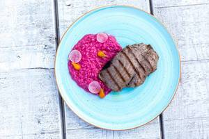 Top view of grilled tuna with beetroot risotto and sweet-lemon foam