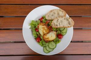 Top view of mixed salad with cucumber, cherry tomato, halloumi cheese and two slices of bread