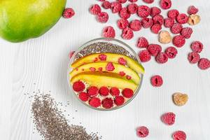 Top view of oatmeal topped with mango, raspberries and Chia seeds (Flip 2019)