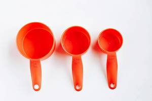 Top view of orange plastic measuring cups on white background.