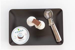 Top View of organic and vegan Nomoo Coconut ice cream and rasps with two scoops, topped with chocolate and ice cream spoon on a black plate