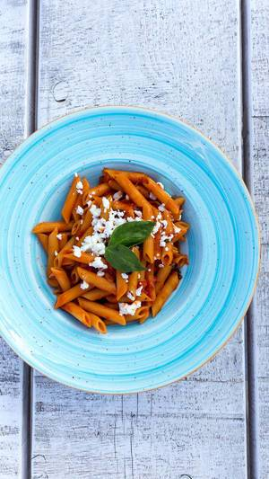 Top view of penne pasta with tomato sauce and grated feta cheese