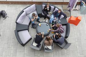 Top view of people on the round garden couch on a terrace of the AXA building, participants of the Barcamp OMWest 2019 in Cologne, Germany