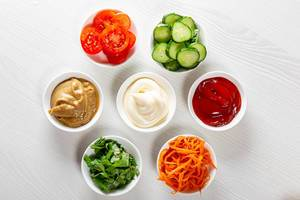 Top view of sauces, sliced vegetables and greens on white wooden background