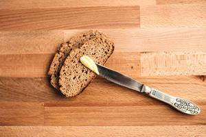 Top view of slices of wholemeal bread with knife and butter on wooden board