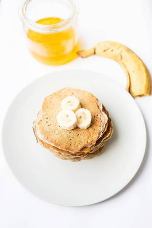 Top view of stacked vegan pancakes with honey and banana  Flip 2019
