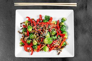Top view of stewed vegetables and mushrooms with sesame seeds on black background with chopsticks