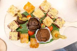 Top view of sweet dessert with fruit cake and chocolate muffins on a wooden board, at AXA
