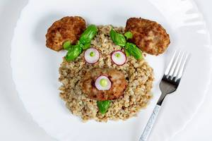 Top view of the face of a bear made of buckwheat porridge, meatballs, vegetables and basil on a white plate