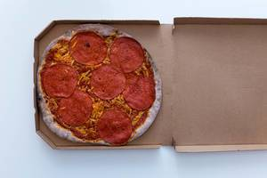 Top view of the new vegan salami pizza by Vapiano, in a take-away cardboard box