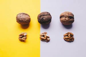 Top view of three whole walnuts on yellow and purple background. Concept food photography