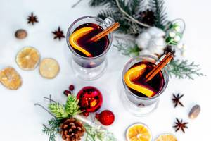 Top view of two glasses of mulled wine with christmas decor on a white background