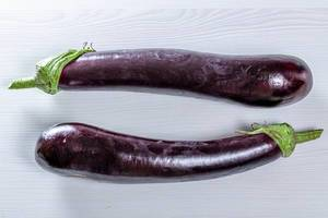 Top view of two purple eggplants on a white table