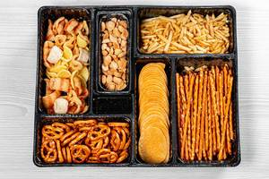Top view of various beer snacks small pretzels, peanuts, potato chips (Flip 2019)
