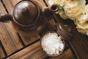 Top view of white powder and teapot on a wooden surface (Flip 2019)