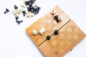 Top view of wooden chess box with figures on white background