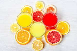 Top view orange, lemon and grapefruit juices with slices of fresh citrus (Flip 2019)