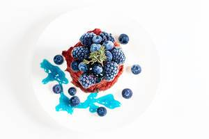 Top view, pancakes on a white plate with blueberries and mulberries