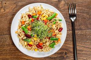 Top view pasta with vegetables on wooden background with fork
