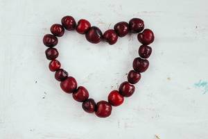 Top View Photo of Cherries forming Heart on White Background