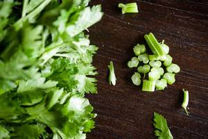 Top View Photo of Chopped Celery next to Bunch of Parsley on Wooden Table