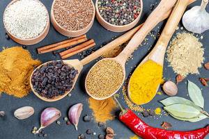 Top View Photo of Curry, Tumeric, Garlic and other colorful spices with Chili, Cinnamon and Wooden Spoons