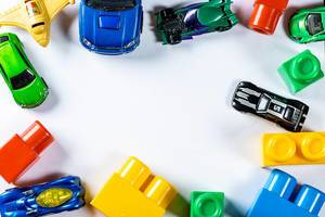 Top View Photo of Different Toys such as Toy Cars and Colorful Building Blocks on White Background