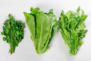 Top View Photo of Fresh Parsley, Romaine Salad and Arugula on White Wooden Background