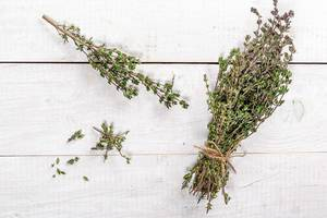 Top View Photo of Fresh Thyme Branches on White Wooden Table