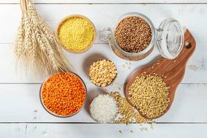 Top View Photo of Grain such as Rice, Wheat, Millet, Lentils, Peas and Buckwheat on white Wooden Table