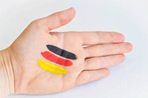 Top View Photo of Hand with Black, Red and Gold Paint in Stripes as Germany Flag