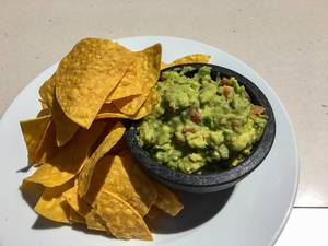Top View Photo of Nachos on a white Plate with Avocado Dip