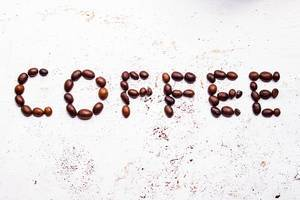 Top View Photo of Roasted Coffee Beans forming the Word Coffee on White Background with Ground Coffee