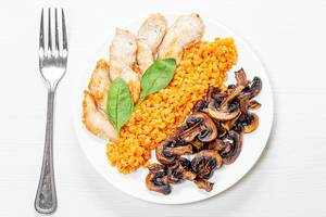 Top view plate with lentils, chicken and mushrooms on a white wooden background (Flip 2019)