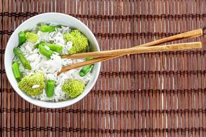 Top view rice with asparagus and broccoli in a bowl with chopsticks