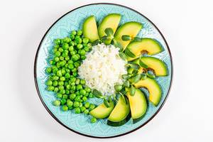 Top view rice with avocado, green peas and sunflower microgreen on a white background