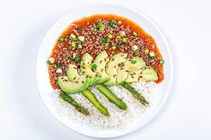 Top view. Rice with tomato-Apple sauce, asparagus, avocado and flax seeds on white background