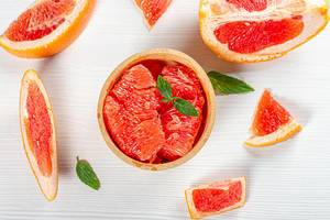 Top view ripe fresh grapefruit slices on white wooden background (Flip 2019)