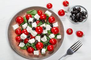 Top-view - Salat mit frischen Tomaten, Oliven, Feta Käse und Basilikum