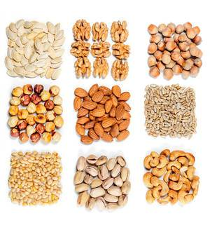 Top view, set of different types of nuts and seeds on a white background