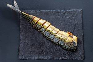 Top view sliced pieces of smoked mackerel on a black background (Flip 2019)