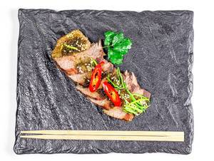Top view, slices of baked beef with leek, hot chili pepper and sesame seeds on a black tray
