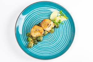 Top view slices of fried hake with Brussels sprouts