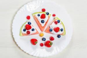 Top view, strawberries, raspberries, blueberries and white cream on slices of ripe watermelon