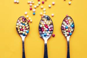 Top view three spoons with colorful sprinkles on yellow background