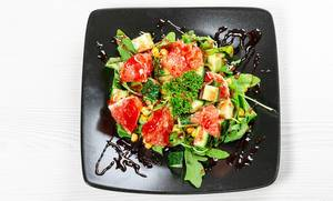 Top view vegetarian salad with arugula, vegetables and grapefruit slices on a black plate (Flip 2019)