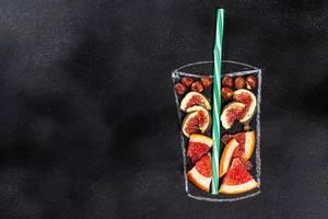Top-view von Feigen, Grapefruit und Haselnüssen in einer Glasumrandung aus Kreide auf schwarzer Tafel und symbolisiert Gesundes-Essen