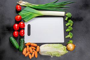 Top view white kitchen Board in collapse of fresh vegetables on black background