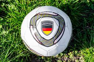 Top views of soccer ball the flag of Germany on green grass