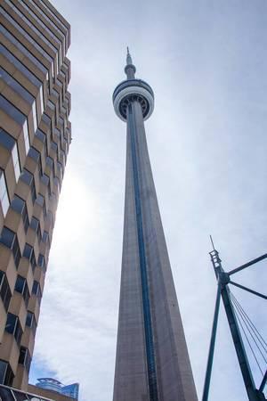 """Torontos Fernsehturm """"CN Tower"""", neben einem Hochhaus und bewölktem Himmel"""